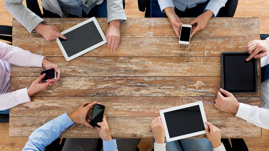 Different hands with mobile phones and tables on a wood table